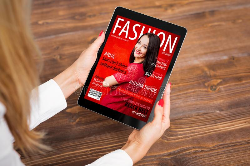 妇女读书在片剂的时装杂志 库存图片