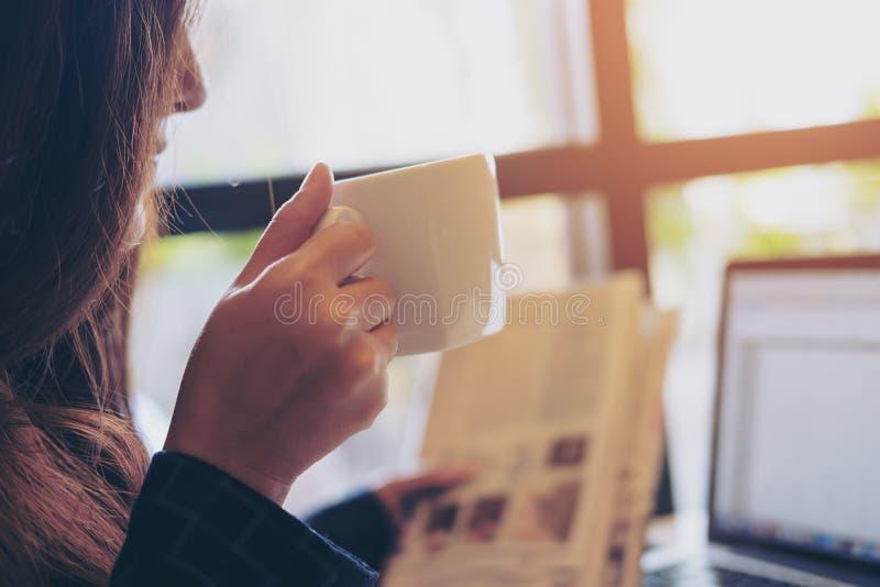 妇女读书报纸和饮用的咖啡,当使用膝上型计算机早晨在办公室时 免版税库存照片