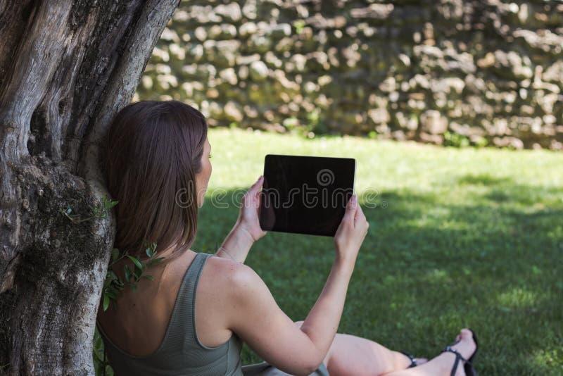 妇女读书片剂和享受休息在公园在树下 图库摄影