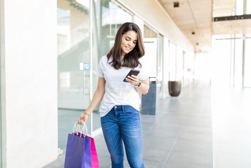 妇女读书电话留言,当运载在购物中心时的购物袋 免版税库存照片