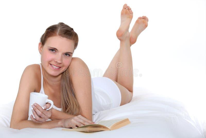 妇女读取和喝 免版税库存照片