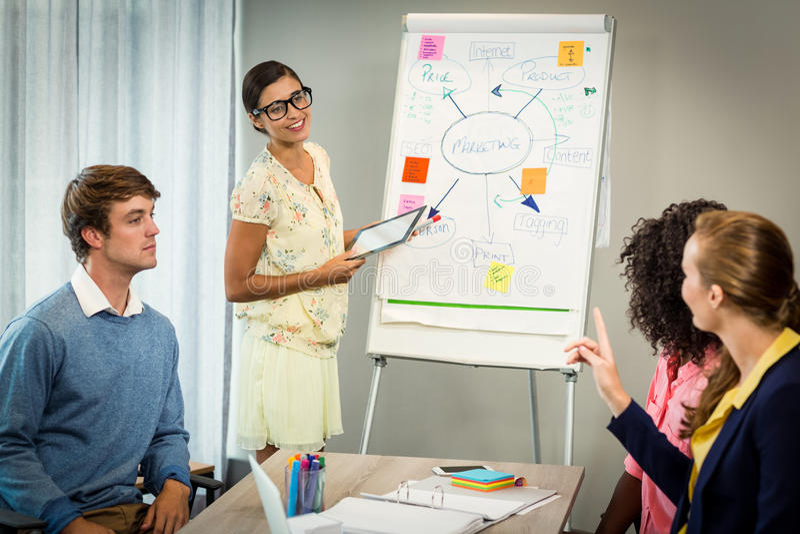 妇女谈论在白板的流程图与工友 图库摄影