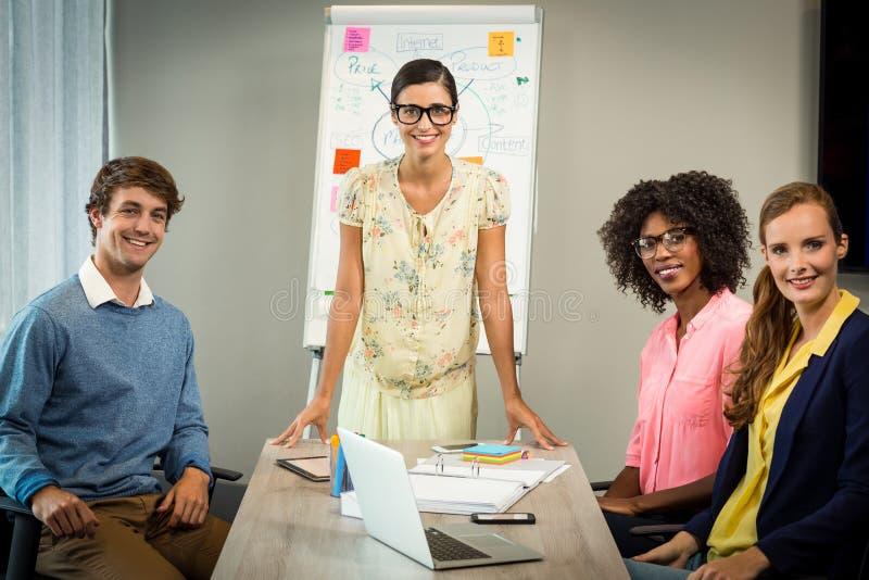 妇女谈论在白板的流程图与工友 库存照片