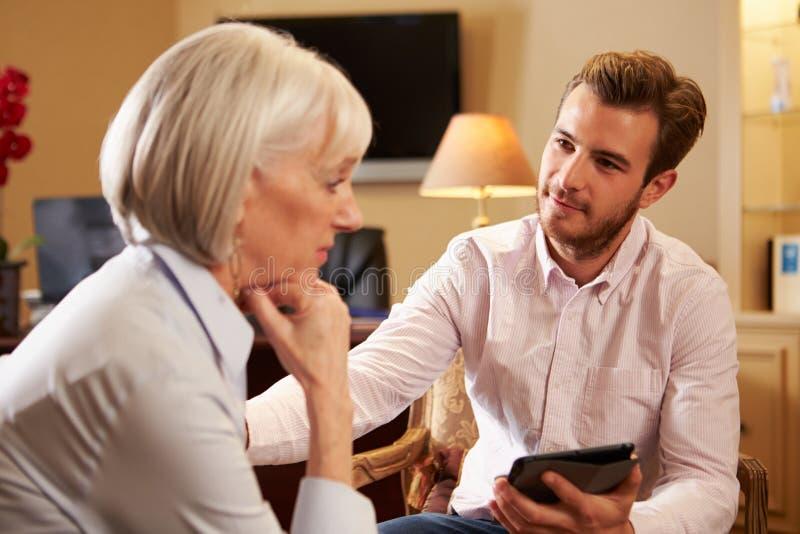 妇女谈话与使用数字式选项的男性顾问 免版税库存照片