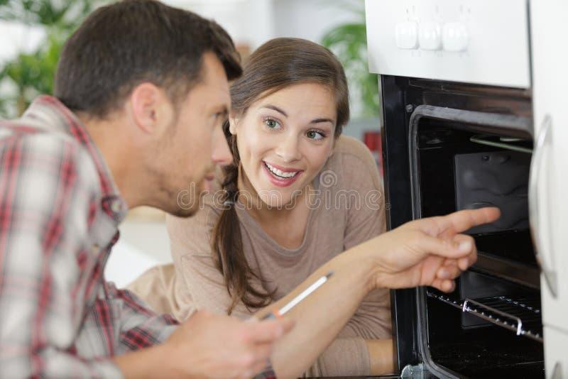 妇女谈话与修理在烤箱里面的男性工作者 免版税库存照片