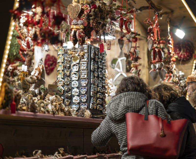 妇女谈话与在圣诞节市场摊前面的朋友身分merano南部的蒂罗尔 库存图片