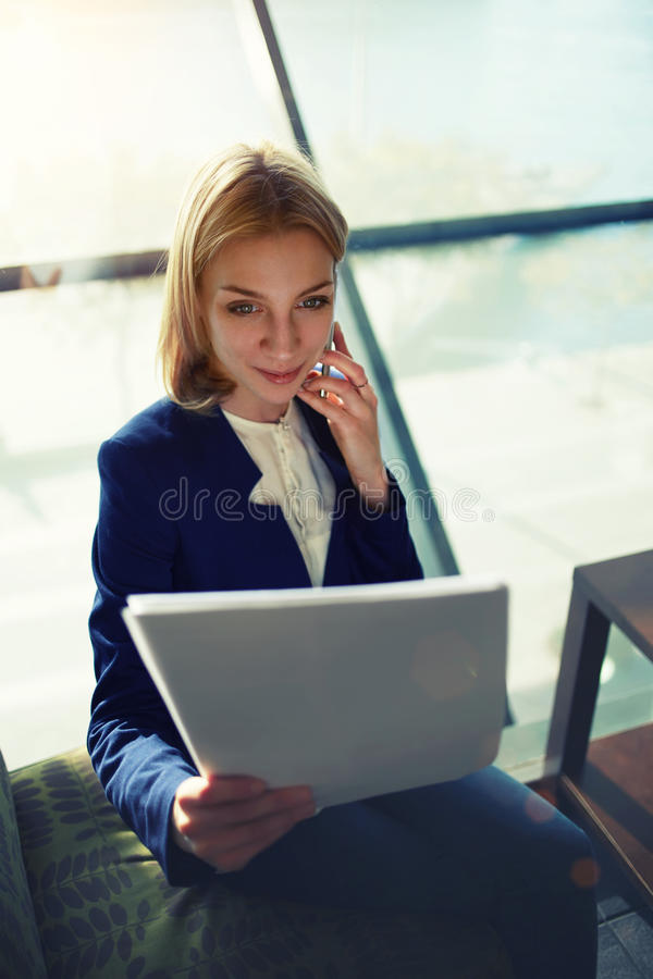 妇女谈话与她丈夫微笑读他文章 免版税库存图片