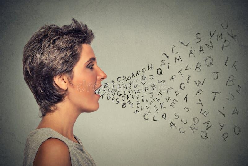 妇女谈话与字母表在从她的嘴出来上写字 免版税库存照片