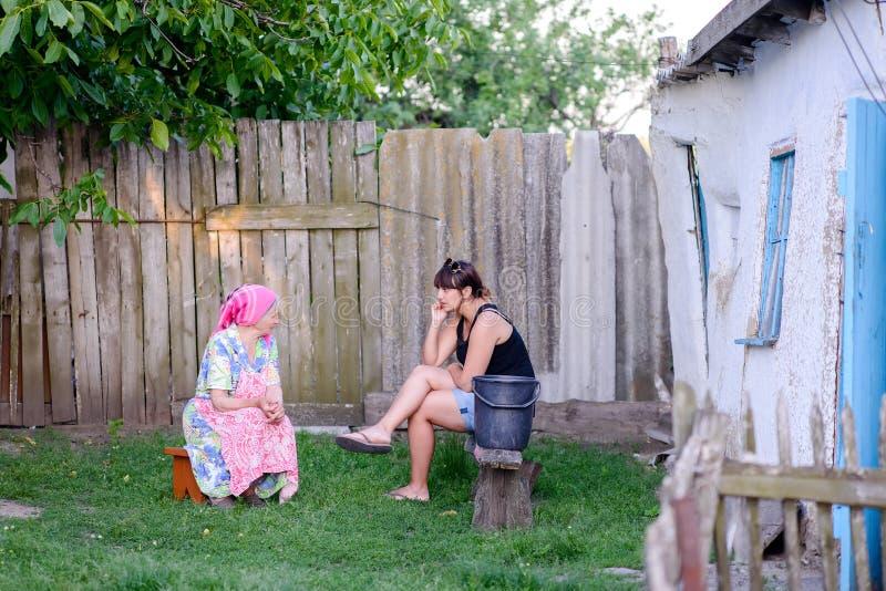 妇女谈话与母亲户外在围场 免版税图库摄影