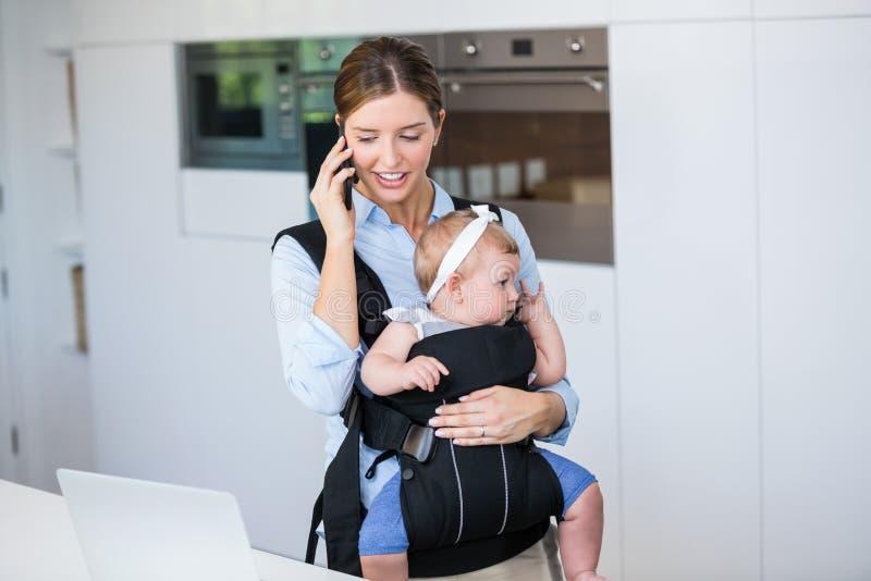 妇女谈话在手机,当运载女婴时 库存图片