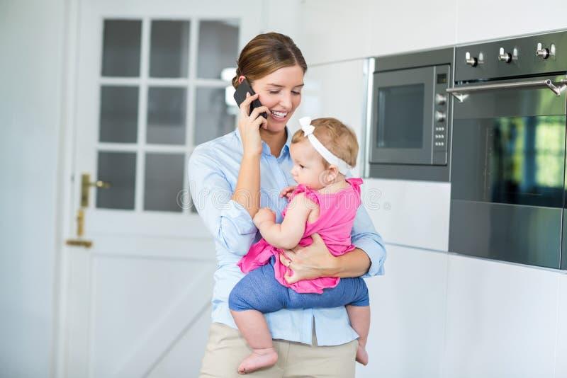 妇女谈话在手机,当运载女婴时 图库摄影