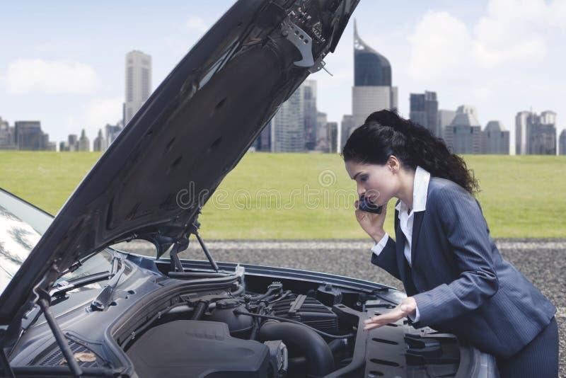 妇女谈话在有残破的汽车的电话 免版税库存图片
