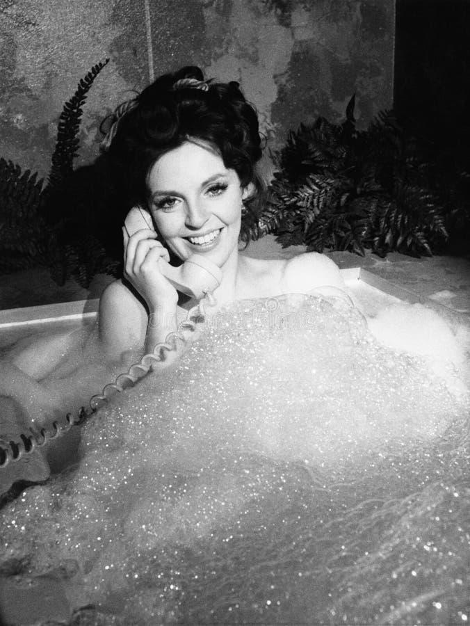妇女谈话在泡末浴的电话(所有人被描述不更长生存,并且庄园不存在 供应商保单那 图库摄影