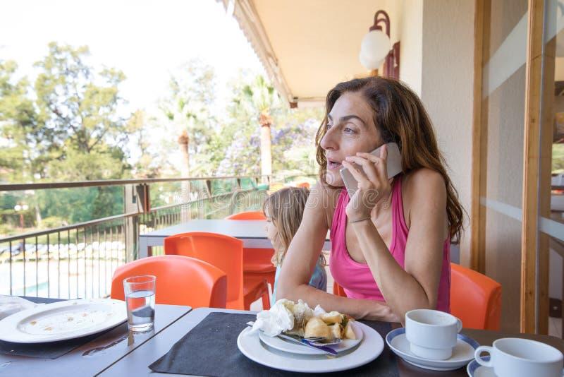 妇女谈话在电话在咖啡馆大阳台  库存图片