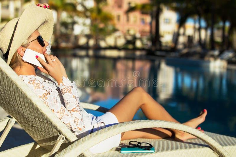 妇女谈话在电话白色放松在豪华旅游胜地旅馆里 图库摄影