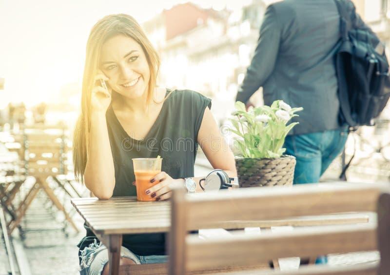妇女谈话在电话,当坐在酒吧时 免版税库存照片