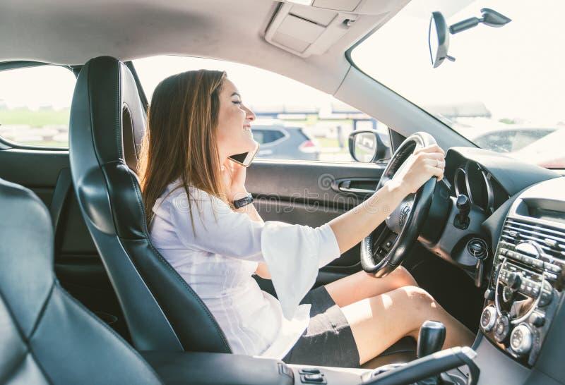 妇女谈话在电话,当驾驶汽车时 免版税库存图片
