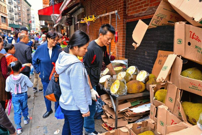 妇女购买留连果果子在小的瓷街道上的停留演出地在曼哈顿有人,纽约人群背景  库存照片