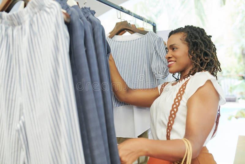 妇女购买衣裳在商店 免版税库存照片
