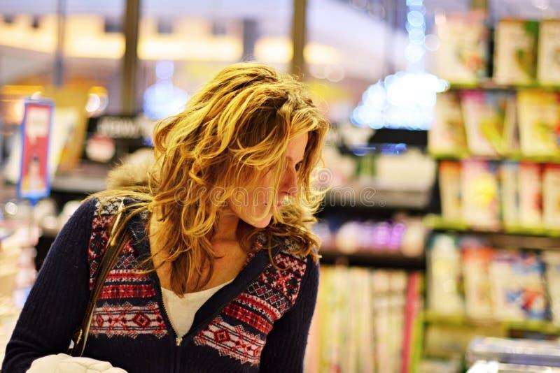 妇女购物在书店 库存照片