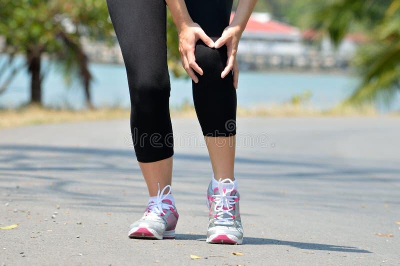 妇女赛跑者举行她的体育伤害了膝盖 免版税库存照片