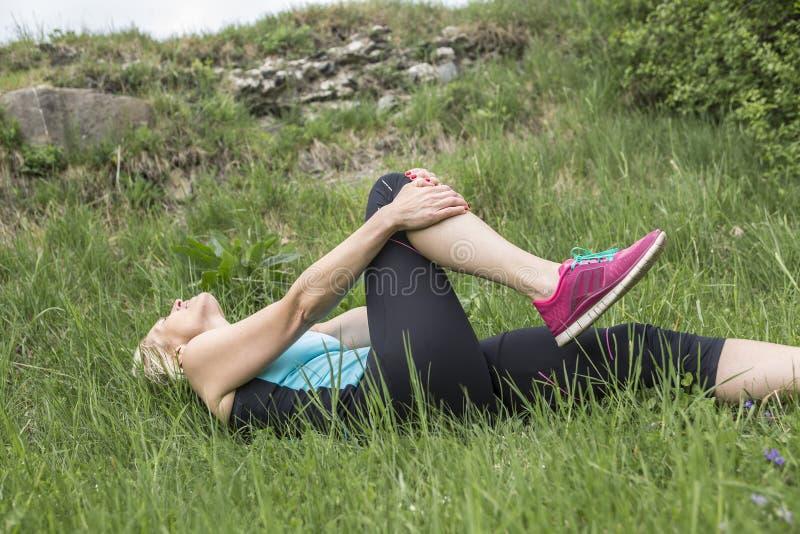 妇女赛跑者举行她的体育伤害了膝盖 库存照片