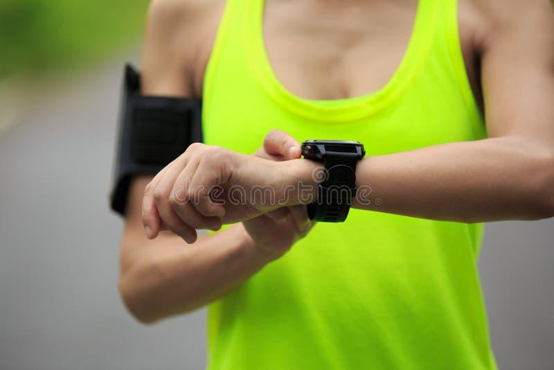 妇女赛跑者在跑前设置了体育手表 图库摄影