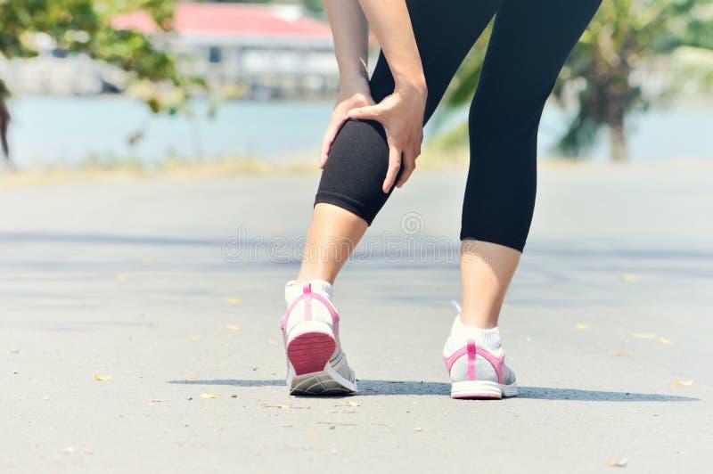 妇女赛跑者在跑期间的腿和肌肉痛户外 库存图片