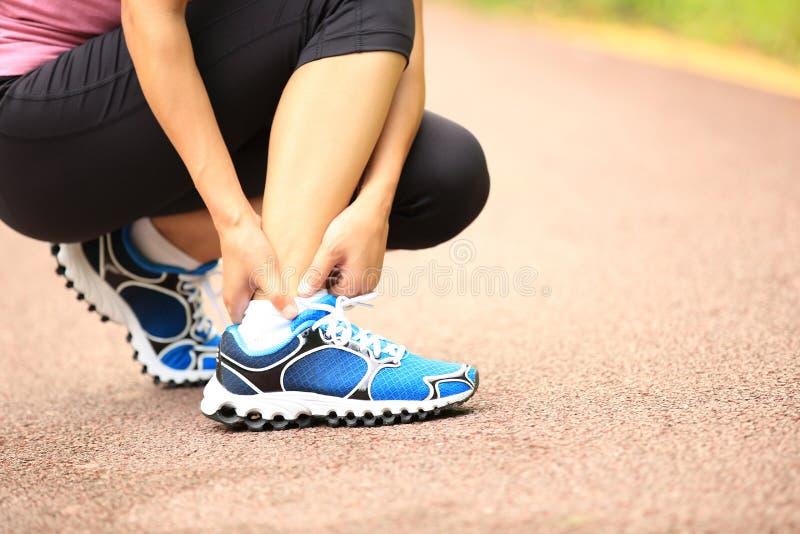 妇女赛跑者持有人她扭转的脚腕 库存图片