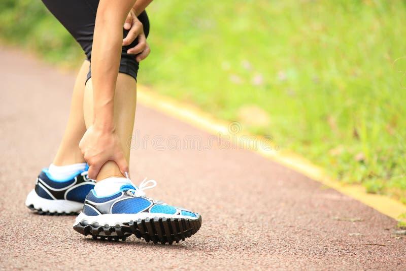妇女赛跑者持有人她扭转的脚腕 免版税库存照片