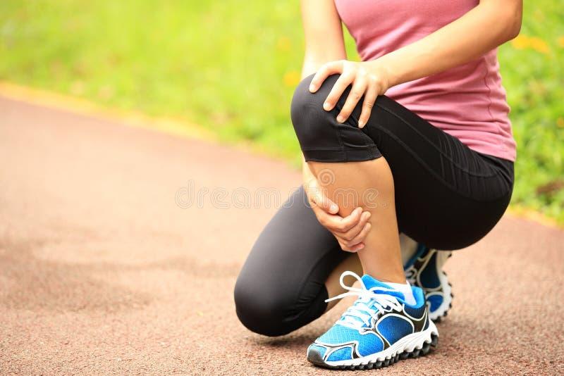 妇女赛跑者持有人她的体育伤害了膝盖 库存图片