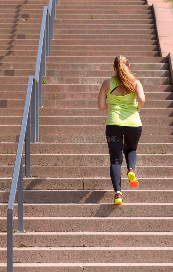妇女赛跑,当攀登台阶在锻炼期间时 免版税图库摄影