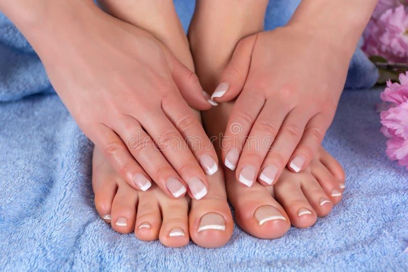妇女赤脚和手有法国指甲油的在蓝色毛巾与桃红色花在演播室 库存图片
