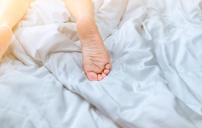 妇女赤脚的关闭在白色毯子和床单的床上在家或旅馆卧室  睡觉和放松概念 免版税库存照片