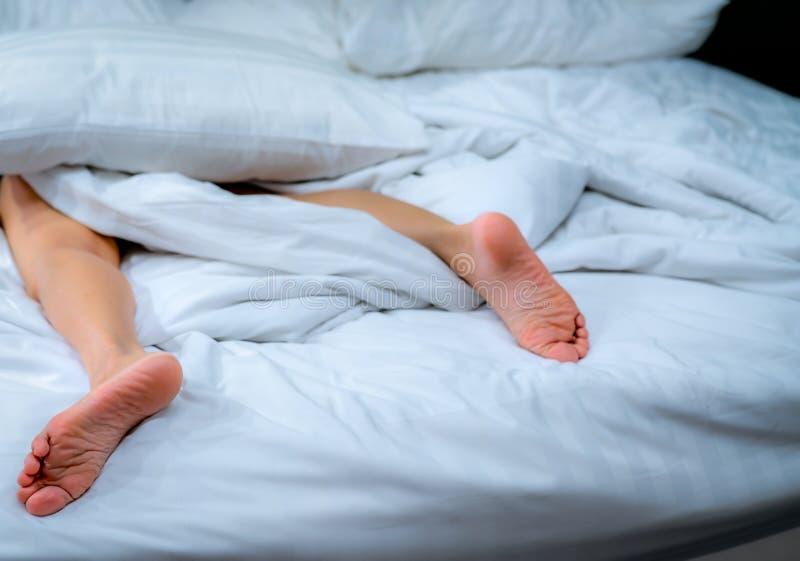 妇女赤脚的关闭在白色毯子和床单的床上在家或旅馆卧室  睡觉和放松概念 免版税图库摄影