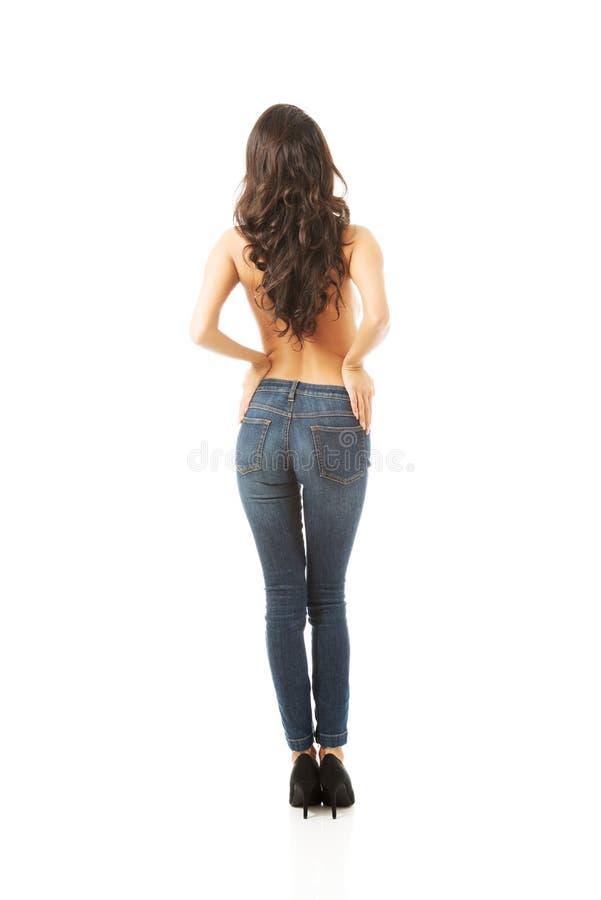 妇女赤裸上身的佩带的牛仔裤后面看法  免版税库存照片