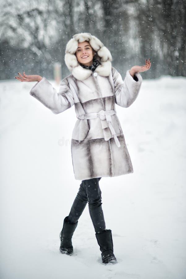 妇女走和获得在雪的乐趣在冬天森林里 免版税图库摄影