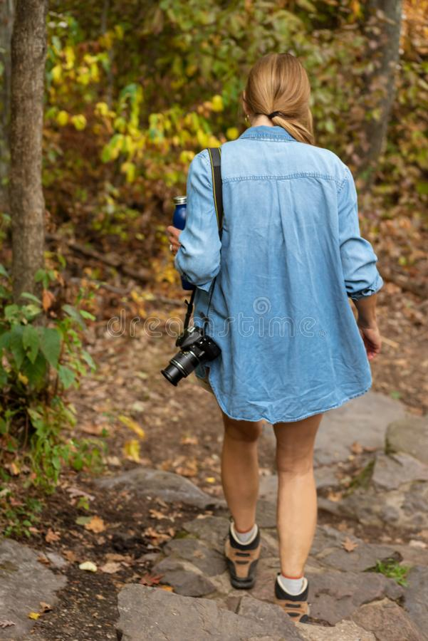 妇女走在森林道路的自然摄影师在秋天与 库存照片