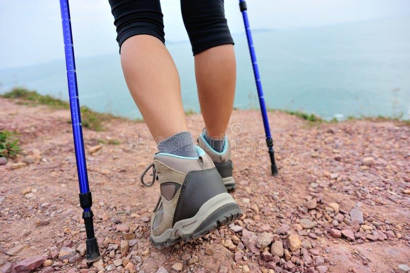 妇女走在海边山行迹的远足者腿 图库摄影