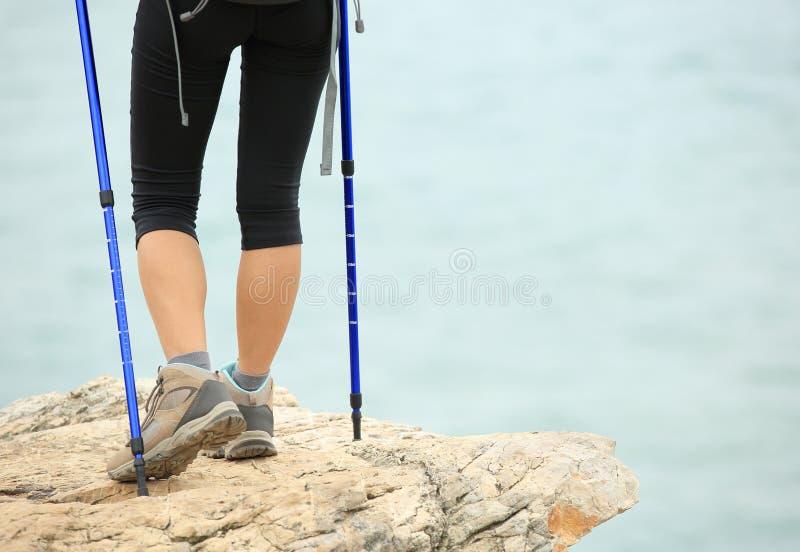 妇女走在海边山行迹的远足者腿 免版税库存照片