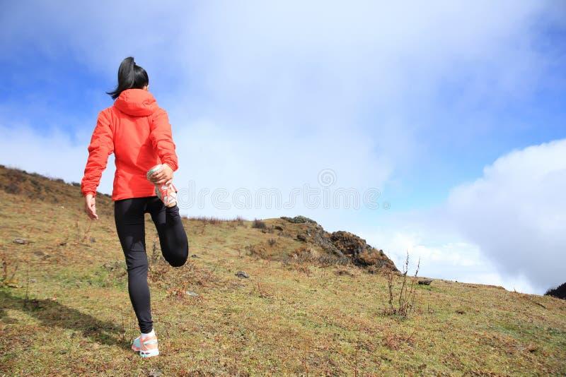 妇女足迹在山峰的赛跑者准备 免版税库存照片