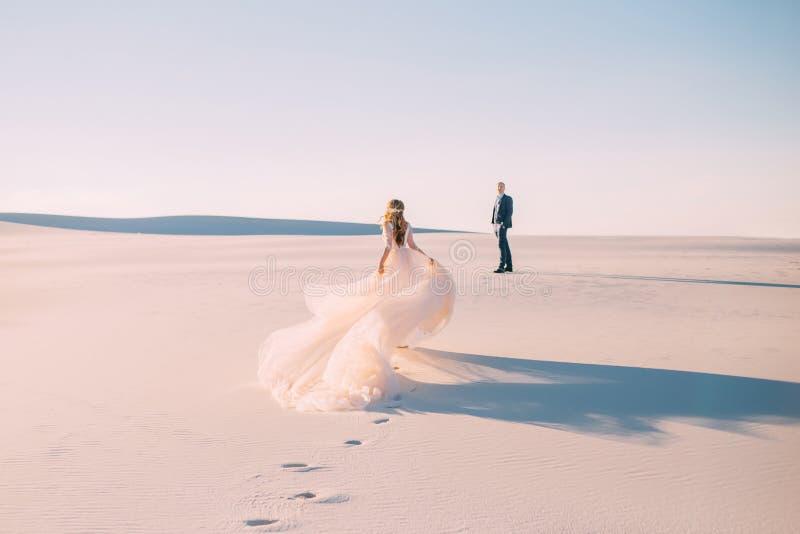 妇女跑遇见一个人 有在风飞行的一把非常长的簪子的礼服 从后面的照片没有面孔 图库摄影