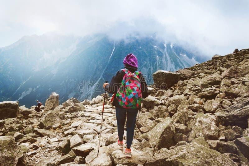 妇女跟踪棍子顶面山登上Rysy的旅客背包 库存照片