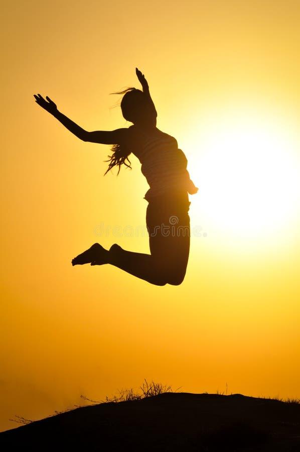 妇女跳和日落剪影 免版税图库摄影