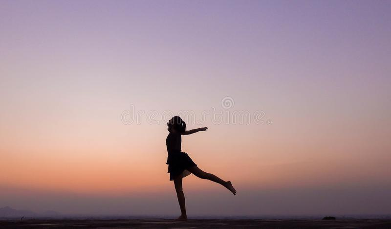 妇女跳舞剪影在日落的 免版税库存图片