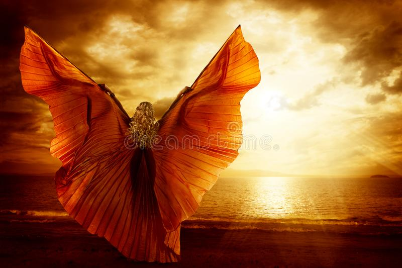 妇女跳舞翼礼服,时尚艺术在海洋天空的模型飞行 库存照片