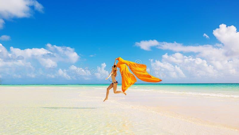 妇女跳跃的跑在蓝天的海滩覆盖背景 免版税库存照片