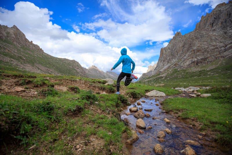 妇女跳过小河水的足迹赛跑者在山 库存照片