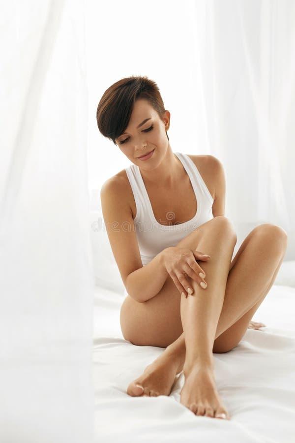 妇女身体关心 接触长的腿软的皮肤的美丽的女孩 免版税库存图片