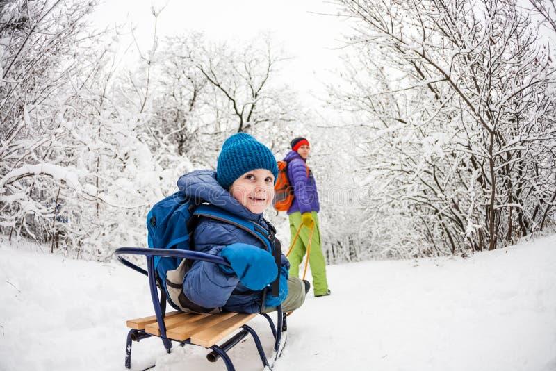 妇女身怀雪撬的一个孩子 免版税图库摄影